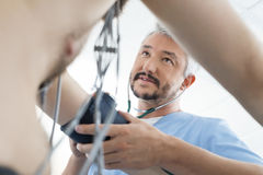 Doctor Looking At Male Patient While Measuring Blood Pressure Stock Photos