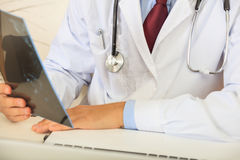 Doctor looking at a mammography. Doctor on his desk looking at a mammography Royalty Free Stock Image