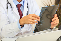 Doctor looking at a mammography. Doctor on his desk looking at a mammography Royalty Free Stock Photos