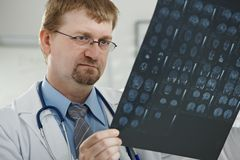 Doctor looking at medical scan Stock Images