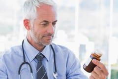Doctor looking at medicine jar Royalty Free Stock Photos