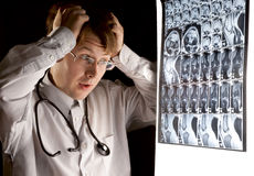 Doctor looking at the MRI scan with panic stock images