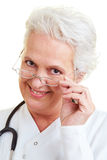 Doctor looking over her glasses Stock Photos