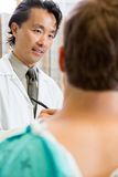 Doctor Looking At Patient While Discussing Report Stock Image
