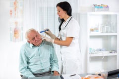 Doctor looking into patient's ear. Female doctor and senior man royalty free stock images