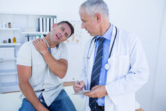 Doctor looking at patient shoulder Royalty Free Stock Photo