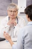 Doctor looking at patient, smiling. Female senior doctor looking at patient, smiling Stock Photos