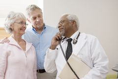 Doctor Looking At Patients While Using Landline Phone. An African American senior male doctor looking at patients while using landline phone Stock Photography