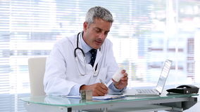 Doctor looking at pills while writing a prescription stock footage