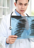 Doctor looking at x ray. Close up potrait of doctor looking at chest x ray Stock Photography