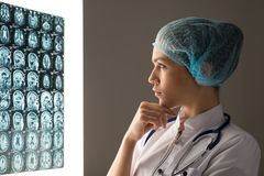 Doctor looking at the x-ray. Female doctor looking at the x-ray image attached to the glowing screen royalty free stock photos