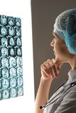 Doctor looking at the x-ray. Female doctor looking at the x-ray image attached to the glowing screen royalty free stock image