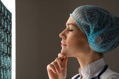 Doctor looking at the x-ray. Female doctor looking at the x-ray image attached to the glowing screen stock photography