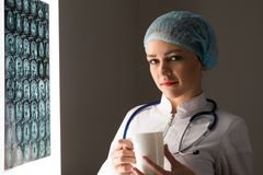 Doctor looking at the x-ray. Female doctor looking at the x-ray image attached to the glowing screen, holding a white mug with a drink stock photography