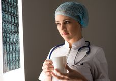 Doctor looking at the x-ray. Female doctor looking at the x-ray image attached to the glowing screen, holding a white mug with a drink stock image
