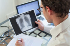 Doctor looking at x-ray of lungs, cancer diagnosis. Doctor looking at x-ray of lungs and writing diagnosis royalty free stock photo