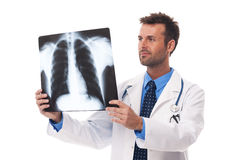 Doctor looking on x-ray. Male doctor examining x-ray image Royalty Free Stock Photo