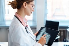 Doctor looking at x-ray picture of a shoulder on her tablet computer. Doctor looking at x-ray picture of a shoulder on her modern tablet computer royalty free stock photography