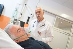 Doctor looking at senior male patient inhaling through oxygen mask. Doctor royalty free stock photography