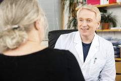Doctor Looking At Senior Patient In Office royalty free stock image