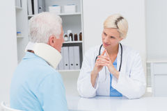 Doctor looking at senior patient wearing neck brace Royalty Free Stock Photography