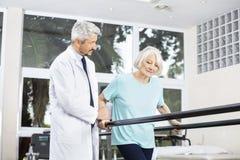 Doctor Looking At Senior Woman Walking Between Parallel Bars. Mature male doctor looking at senior women walking between parallel bars in fitness studio at rehab Stock Photo