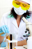 Doctor looking at a test tube of yellow solution Royalty Free Stock Photography