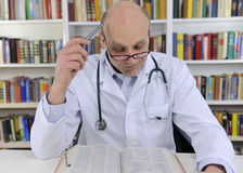 Doctor looking up information on medicine Royalty Free Stock Photo