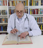 Doctor looking up information on medicine Stock Images