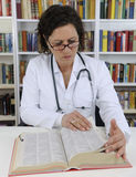 Doctor looking up information on medicine Stock Image