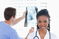 Doctor looking at a of X-ray while his colleague is posing Royalty Free Stock Photos