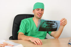 Doctor looking at x-ray while sitting on desk Royalty Free Stock Image