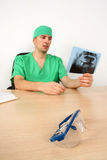 Doctor looking at x-ray while sitting on desk Royalty Free Stock Photography