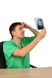 Doctor looking at x-ray while sitting on desk Stock Photography