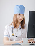 Doctor looks at a computer monitor Stock Photography