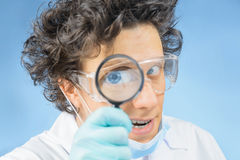 Doctor looks through a magnifying glass Royalty Free Stock Photos