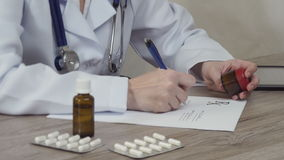 The doctor looks at medicine and writes a prescription. stock footage