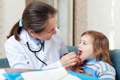 Doctor looks mouth of  child Royalty Free Stock Images