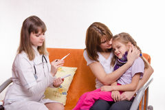 Doctor looks temperature on a thermometer sick girl and her mother comforts Stock Photos