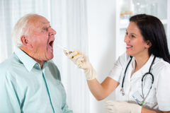 Doctor looks in the throat an older man Royalty Free Stock Photography