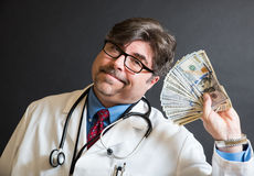 Doctor with lots of cash Stock Images