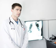 Doctor at lung X-ray. Young doctor standing beside the lung x-ray image Royalty Free Stock Photos