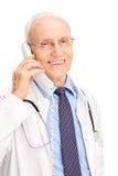 Doctor maduro que habla en un teléfono y una sonrisa Imagenes de archivo