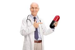 Doctor maduro que sostiene una píldora enorme Imágenes de archivo libres de regalías