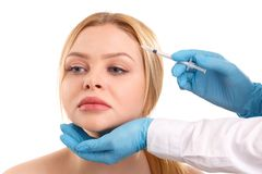 The doctor makes a Botox injection to attractive woman. Isolated. royalty free stock image