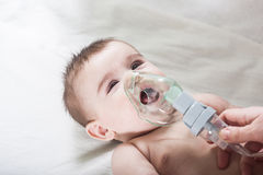 Doctor makes inhalation to a sick little baby. Health care and medicine concept at pediatrician department Stock Image