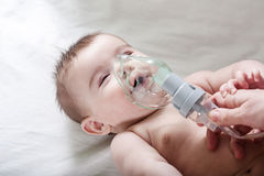 Doctor makes inhalation to a sick little baby. Healthcare and medicine concept at pediatrician department Stock Photos