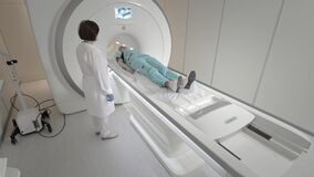 Doctor makes an MRI scan for a patient in a clinic. The girl lies in the MRI device. Magnetic resonance imaging in the