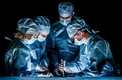 The doctor makes sternotomy during a thoracic operation. Doctors are dressed in blue surgical suits, on their faces they have medical masks, and on their heads Royalty Free Stock Photography