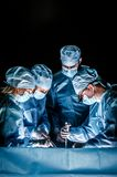 The doctor makes sternotomy during a thoracic operation. Doctors are dressed inone-off blue surgical suits, on their faces they have medical masks, and on Royalty Free Stock Photography